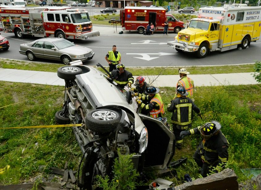 Firefighters work to free a man from a rollover near the Rexford Bridge Wednesday