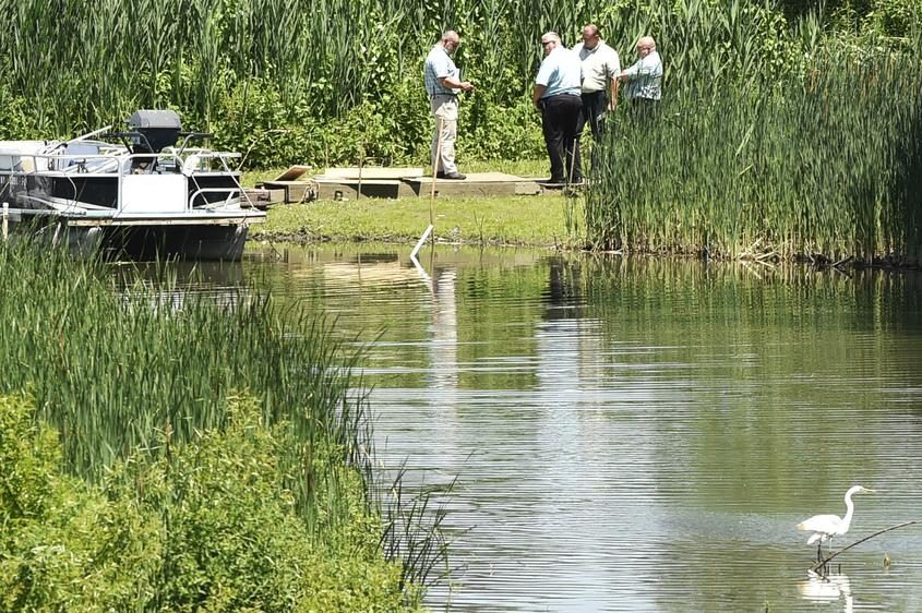 Emergency response officials investigate the area where a body was found Friday in the Mohawk River.