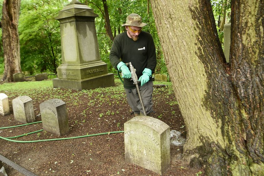 Davey Tree Expert Co.'s Seth Nalven injects pesticide into the roots of a hemlock tree in Vale Cemetery on July 5, 2018.
