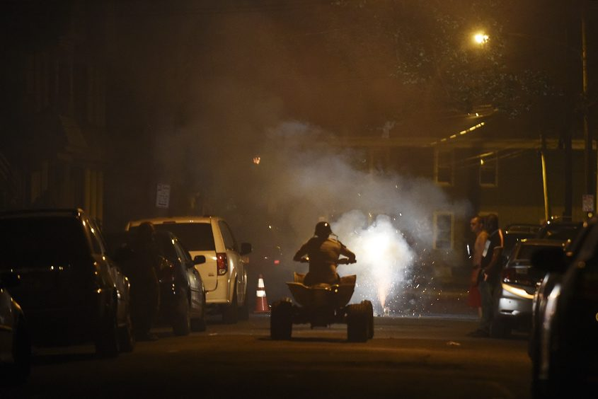 Illegal fireworks are set off on Stanley Street in Schenectady on July 4 as an ATV rider pauses to watch.