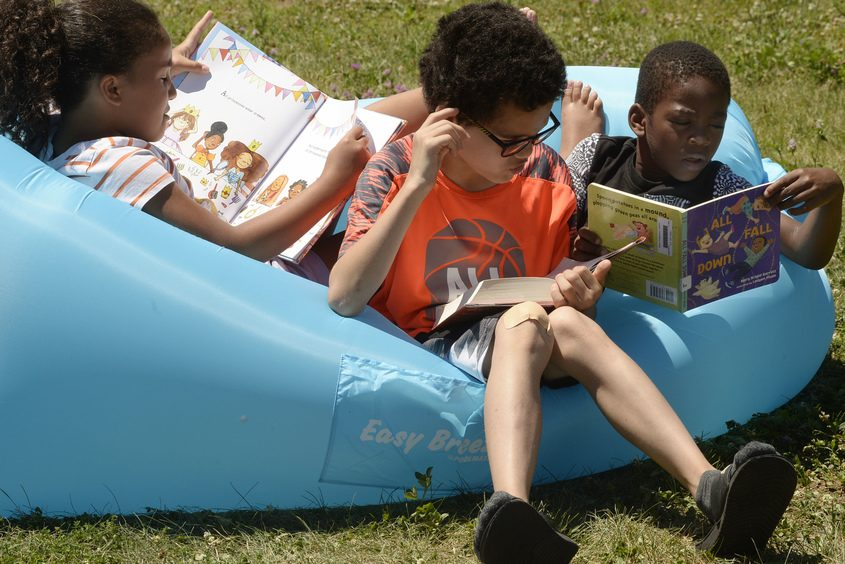 Semira Threatt, 7, left, Tremon Threatt, 11, and Nahmir Brown, 9, huddled together to read at Summer Reading and Ballin'.