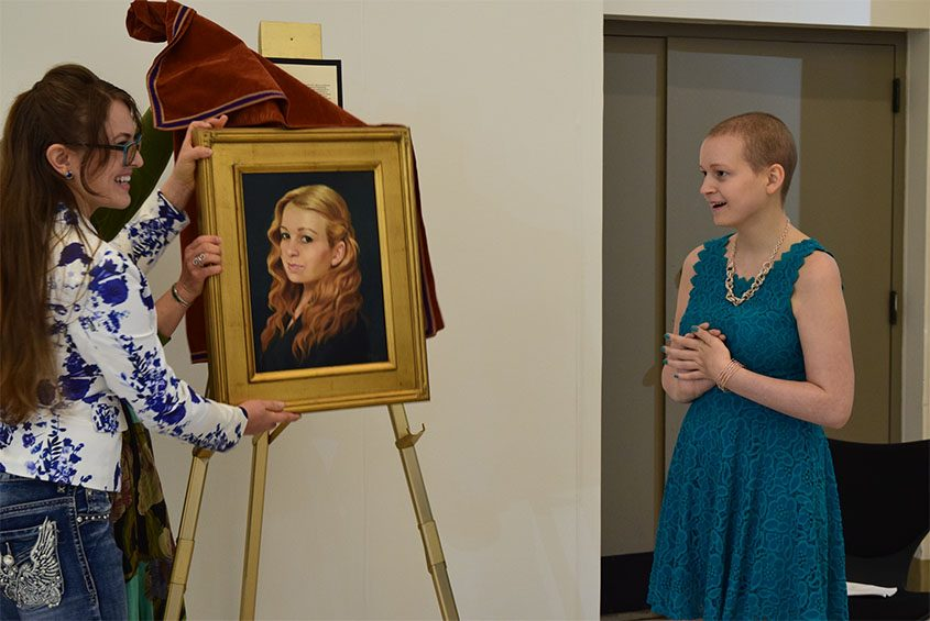 Kaitlin Salomon, right, reacts with joy Friday morning as Kristen Eisenbraun unveils a portrait of her painted by Leslie Peck.