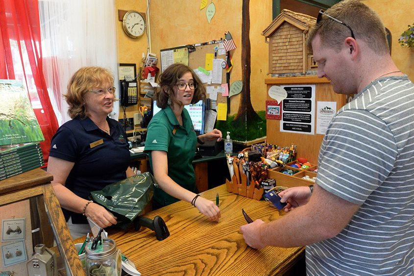 Impressions owner Marianne Barker, left, cashes customers out at the store on Sunday, Aug. 26, the day after the Travers.