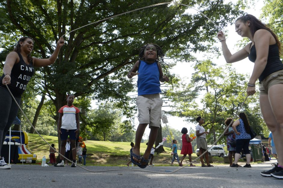 Tashika Frazier, left, and Tiana Miller let youngsters double Dutch at the bookmobile block party in Central Park Tuesday.