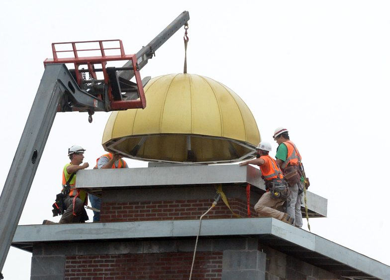Construction crews install a dome to the top of the new Amtrak building being built on Erie Blvd. on Thursday