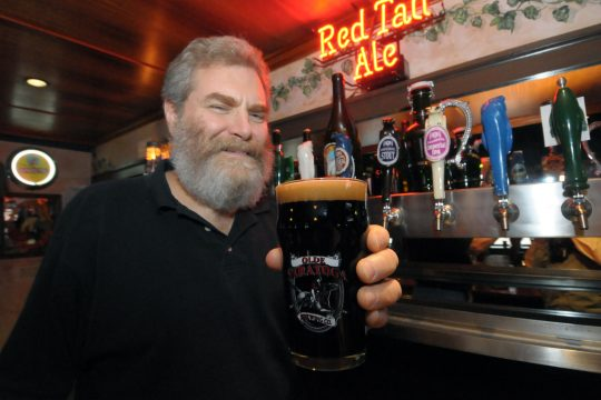 This file photo shows Paul McErlean of Olde Saratoga Brewing Co. in Saratoga Springs with an Imperial Stout the company brewed.