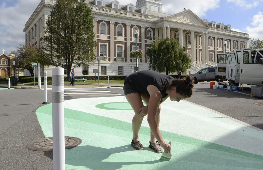 Kristin Bodden of Capital Roots paints a section of a crosswalk on Jay Street earlier this month.