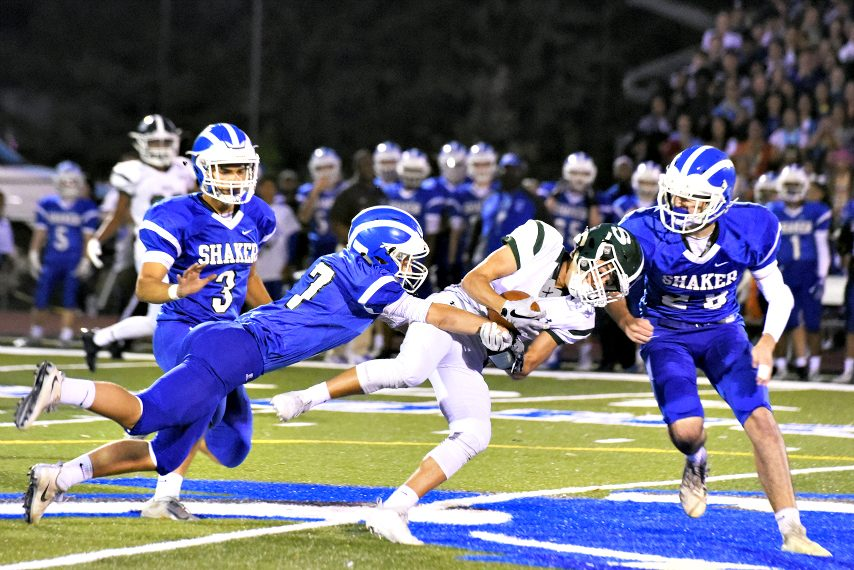 Shaker's Shane Lavender and Amos Grimm tackle Shenendehowa's Josh Szwarcberg during Friday's Class AA football game.