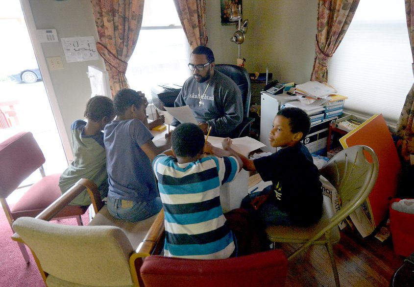 William Rivas works with kids after school at the COCOA House on Stanley Street.