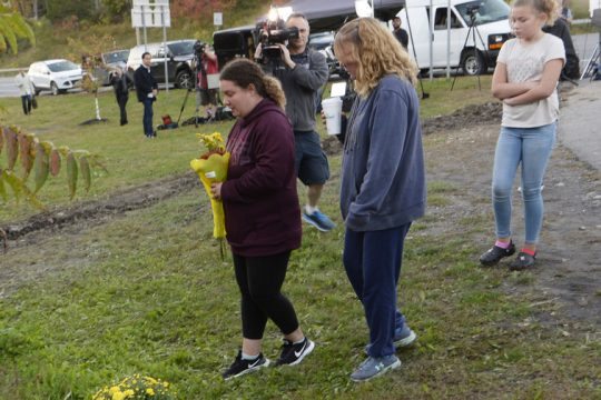 Relatives of victims of yesterday's crash in Schoharie County lay flowers at a memorial