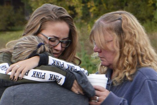 Relatives of victims of Saturday's crash in Schoharie County console each other in front of the Apple Barrell Cafe