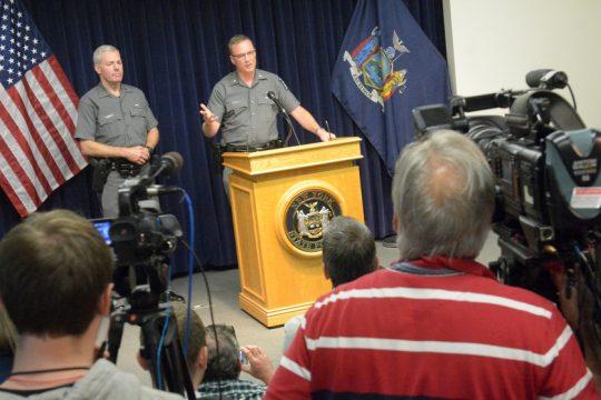 Major Robert E. Patnaude, Troop G Commander, briefs the press Monday