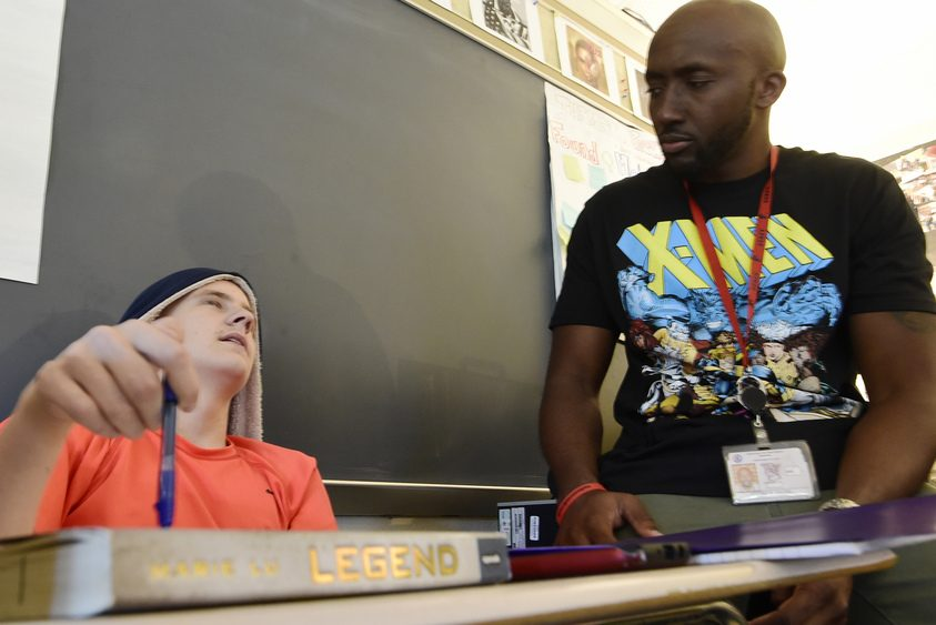"""Schenectady High student Jacob Dillenbeck goes over the book """"Legend"""" with English teacher Andrew Davis Friday."""