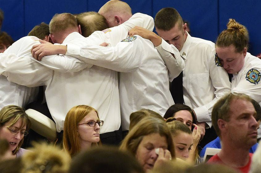 Central Bridge firefighters embrace during the singing of the Bill Withers song 'Lean on Me' Wednesday.