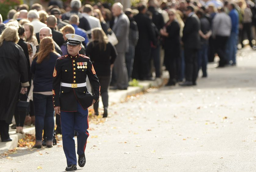 A Marine walks past hundreds of mourners lining the sidewalk along Cornell Street in Amsterdam.