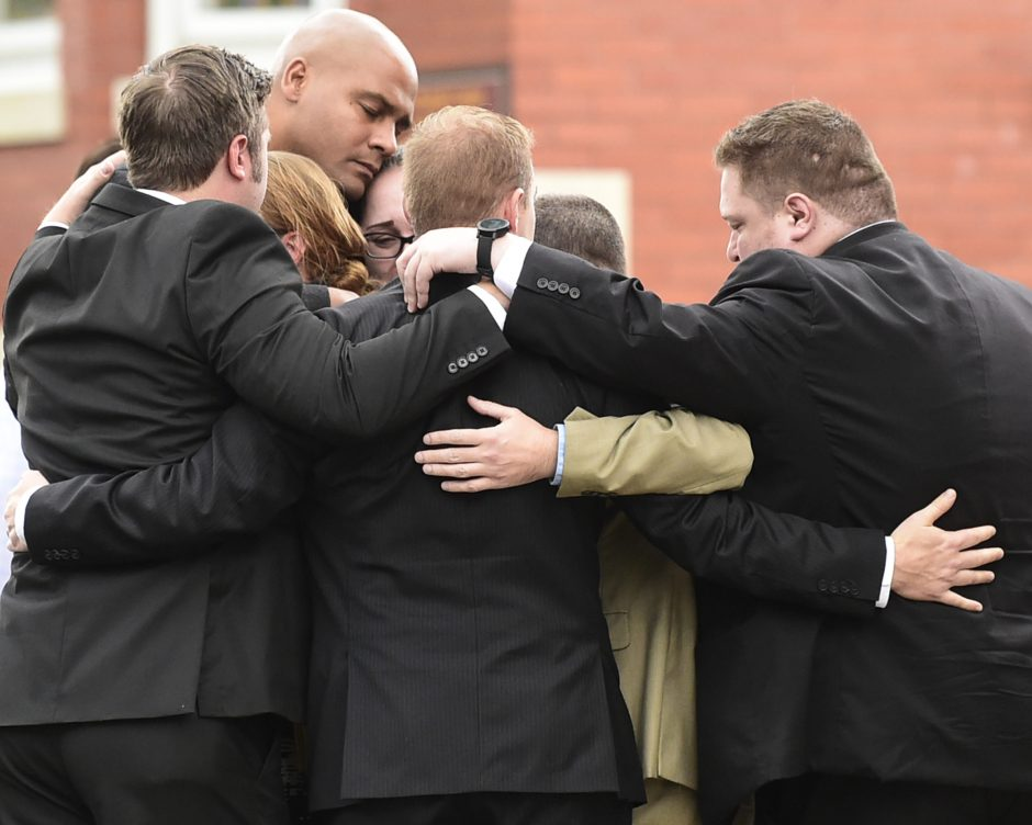 Mourners embrace at St. Stanislaus Roman Catholic Church on Cornell Street in Amsterdam Saturday.