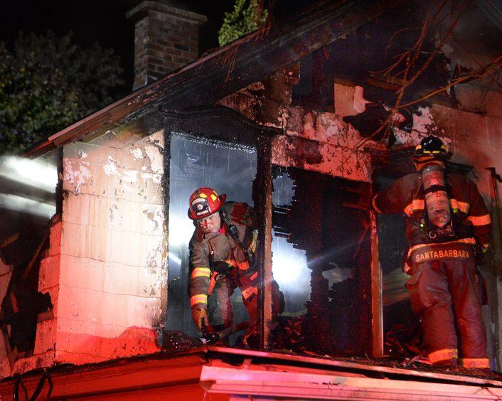 Schenectady firefighter Capt. Joel Metz picks up a hose line while battling the fire