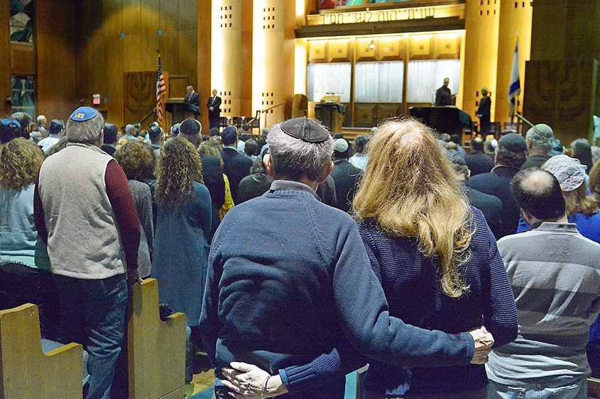 Jeffrey and Marsha Strosberg, members of Temple Israel of Albany, hold each other during a prayer vigil on Sunday.