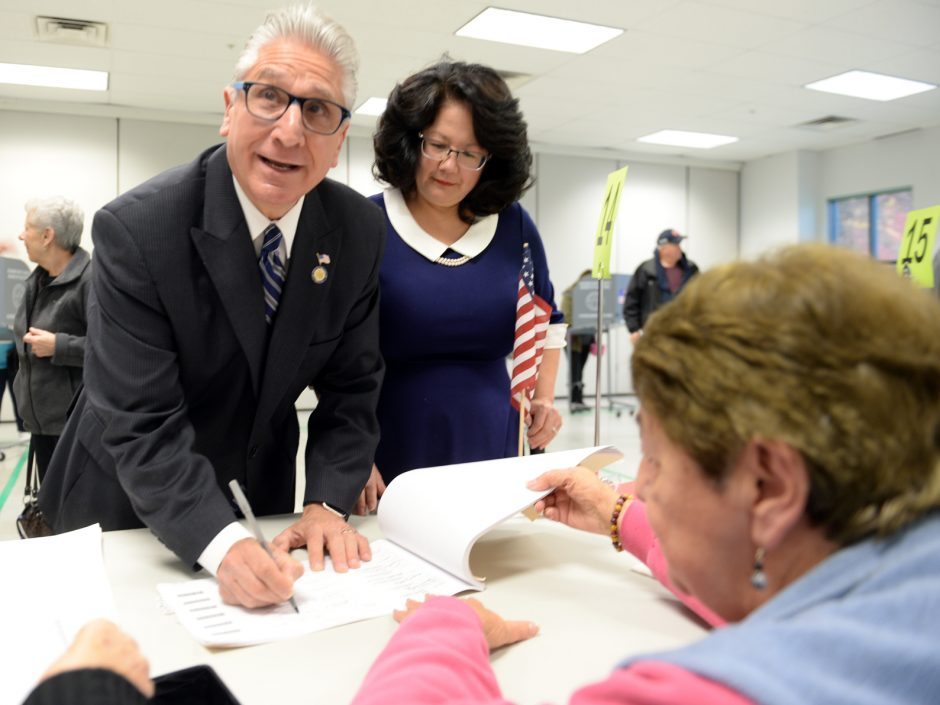 Sen. James Tedisco signs in with his wife Mary Song, during heavy voter turn out at the Glenville Senior Center on Tuesday.