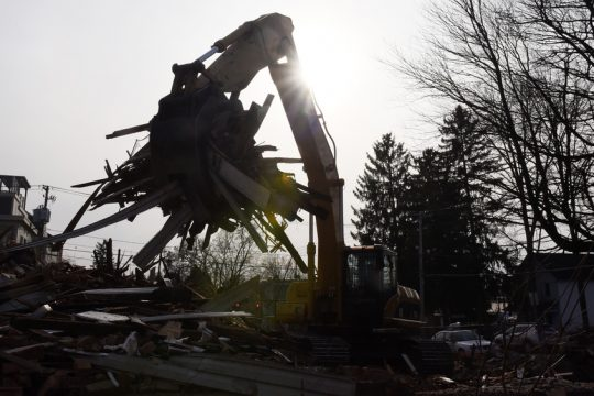 Employees with Schenectady's Jackson Demolition demolish a house at Clinton and Walton streets in Saratoga Springs Monday