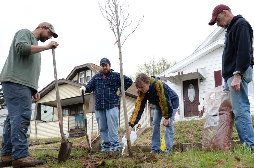 Betsy Henry, center right, plants a tree in front of a home on Schuyler Street in Mont Pleasant in this 2014 file photo.