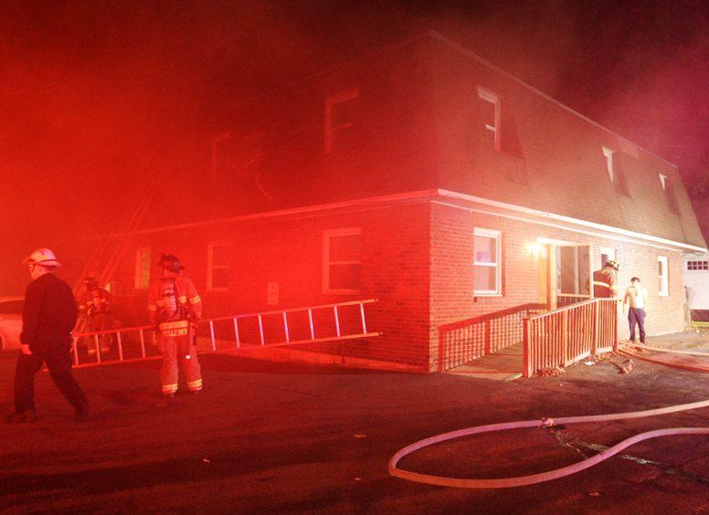 Smoke envelops the apartment building at Van Vranken Avenue after a fire