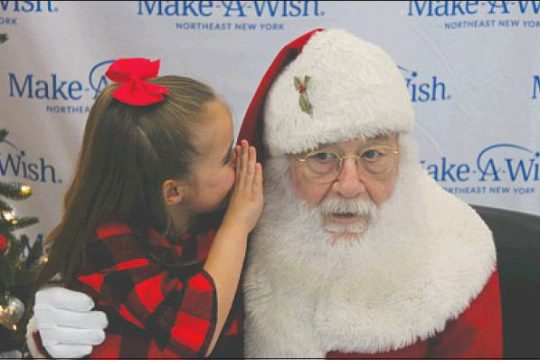 Make-A-Wish Northeast New York wish kid Emma Duncan, 8, of Niskayuna shares a secret with Santa at a recent Make-A-Wish event