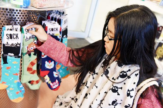 Evelyn Zou, 16, of Clifton Park considers socks for a Secret Santa gift while shopping at ta-da! at Clifton Park Center Sunday.