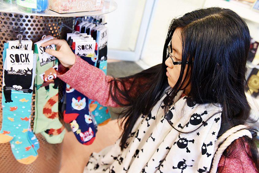 Evelyn Zou, 16, of Clifton Park considers socks for a Secret Santa gift while shopping at ta-da! at Clifton Park Center Sunday.
