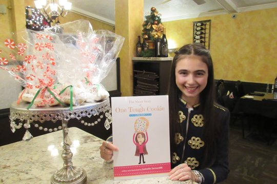 """Isabella Sementilli, 15, of Niskayuna holds her book """"One Tough Cookie,"""" which she wrote and illustrated."""