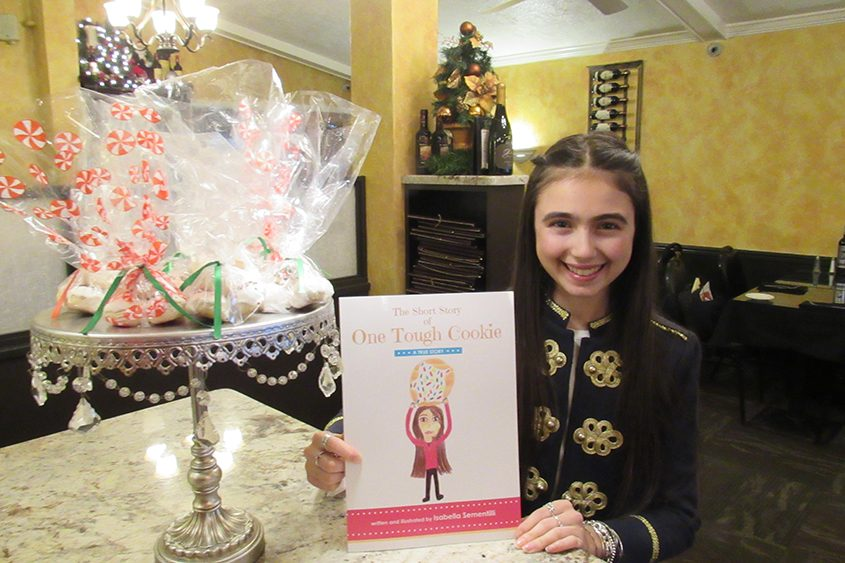 "Isabella Sementilli, 15, of Niskayuna holds her book ""One Tough Cookie,"" which she wrote and illustrated."