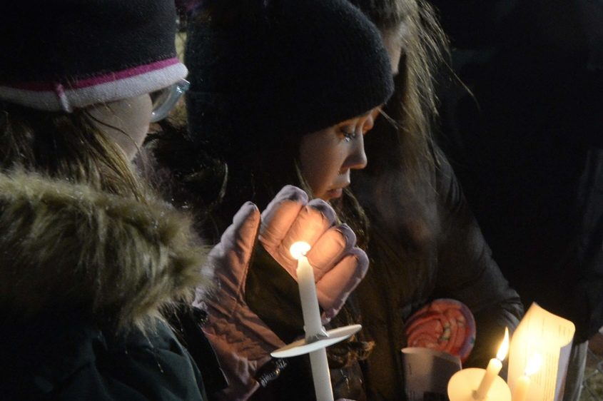 Isabella Kaldy, center, Emma Jones' friend, holds a candle in her memory at a vigil at the Ballston Spa High football field.