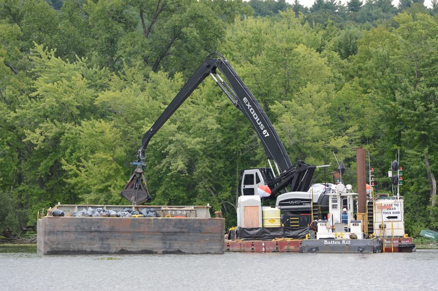 A worker on the Hudson River dredging project shovels stone on a barge in 2013.