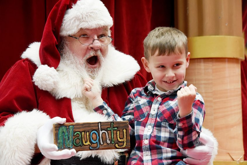 Jayce Varney, 5, of South Glens Falls, poses with Santa tugging his beard on Sunday at the Wilton Mall.