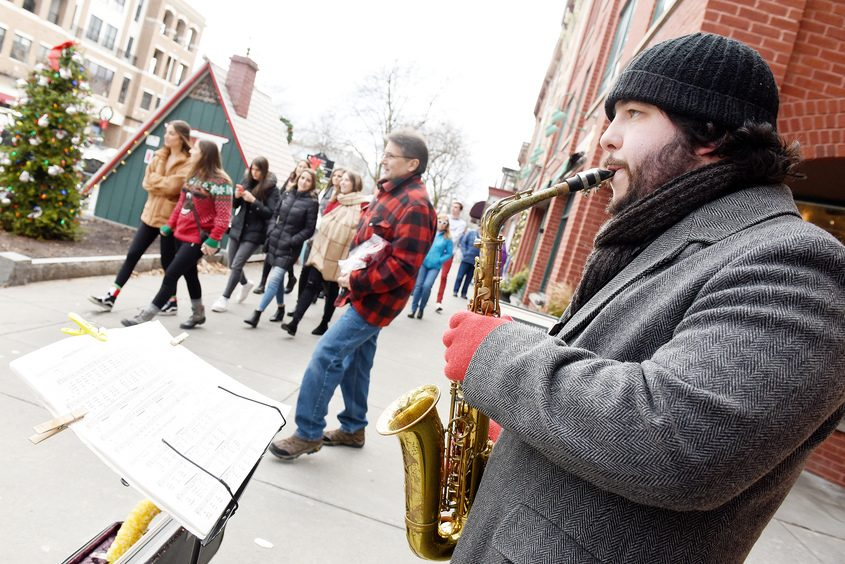Kevin Warren, of Greenwich, plays Christmas tunes on his saxaphone for people outside on Broadway in Saratoga Springs.