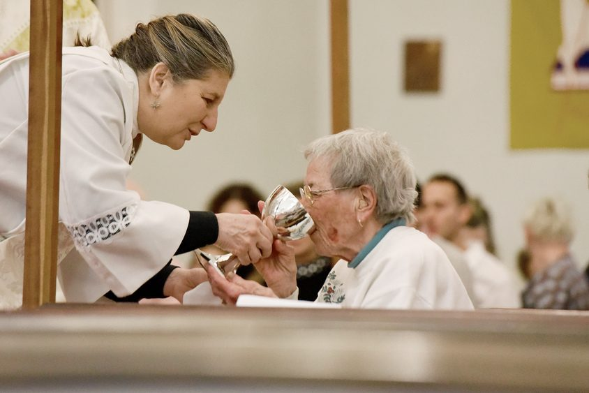 Deacon Rev. Laurie Barlett gives communion during a Christmas Eve service at Episcopal Church.
