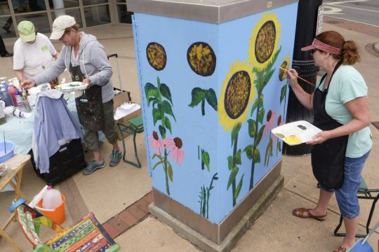 Laurel-Lee Lipski, left, Carole Warburton and Deb Carpenter paint a traffic signal box in August.