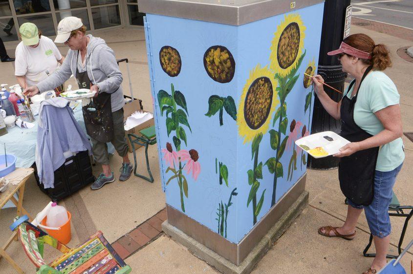 Laurel-Lee Lipski, left, Carole Warburton and Deb Carpenter paint a traffic signal box in August.