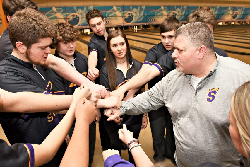 Saratoga Central Catholic athletic director Phonsey Lambert huddles with the bowling team he coaches.