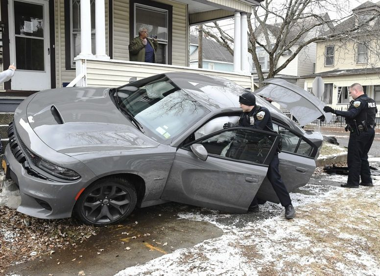 Schenectady Police officers Peter Verret and Christopher Wilgocki search a car that struck a porch Sunday