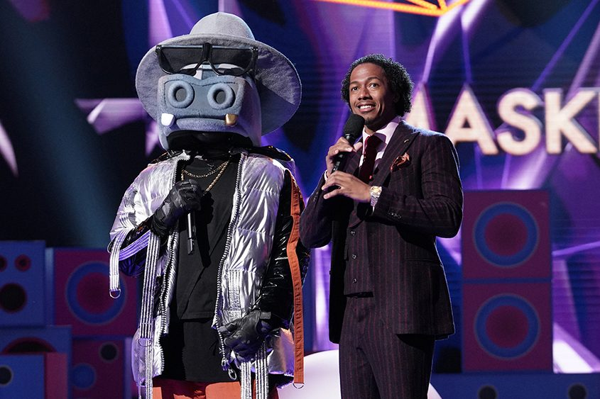 """Host Nick Cannon and a competitor on """"The Masked Singer."""""""