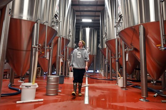 Jacob Jenkins walks within the fermenters in the brew house at Single Cut North Brewery in Clifton Park.