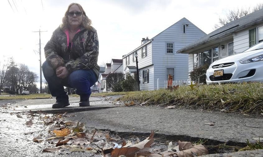 Carol Ellis, of 1181 McClellan St., Schenectady, shows the condition of a sidewalk in disrepair in front of her home Wednesday.