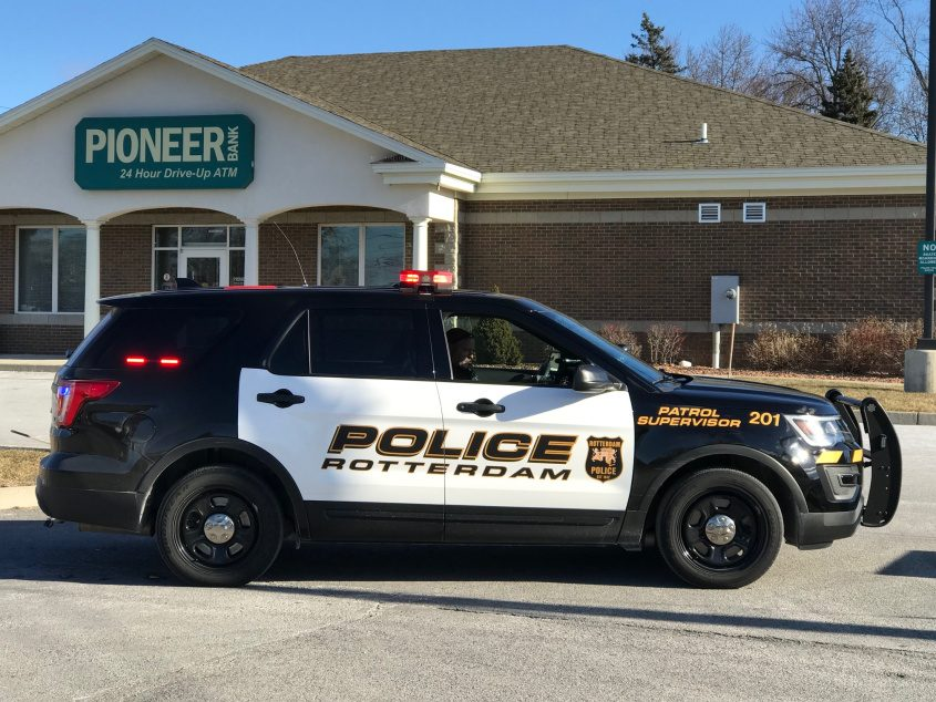 A police officer stands watch outside a Pioneer bank branch in Rotterdam that was robbed Friday morning.