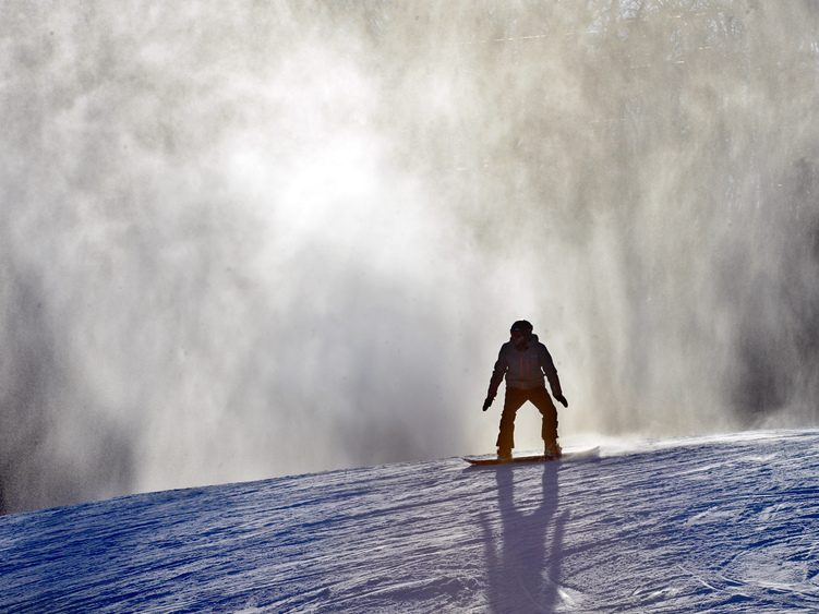 A snowboarder prepares to take a run down the mountain as freshly-made snow blows in the background.