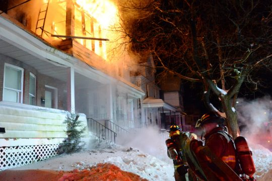 Schenectady firefighters carry a hose line to 1822 Avenue A as flames pour from a second-floor porch Monday