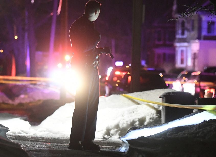 A Schenectady police officer searches for evidence in the wake of the shooting.