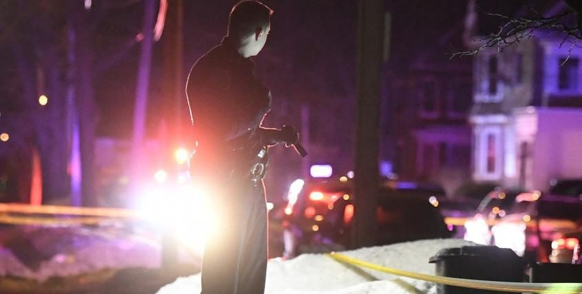 A Schenectady police patrolman looks for evidence at the scene of Friday's shooting death.