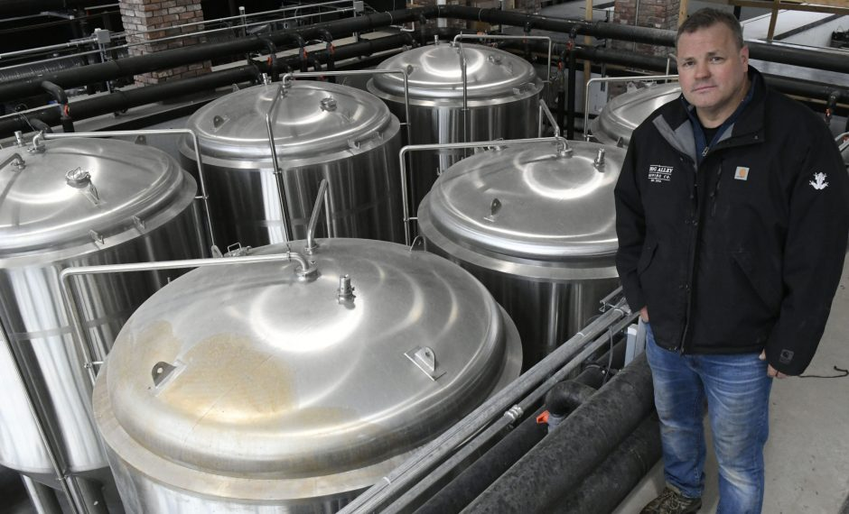 Frog Alley Brewing Co. owner JT Pollard stands above tanks in the new brewary on lower State Street, February 13, 2019.