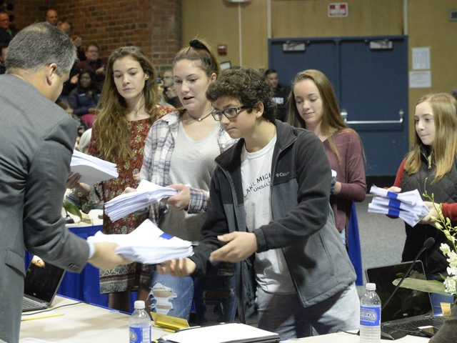 Saratoga High students deliver signed petitions in favor of arming resource officers on school grounds.